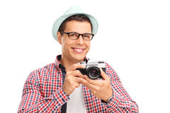 Male photographer holding a camera. Studio shot of a male photographer holding a camera and posing isolated on white background Royalty Free Stock Photography