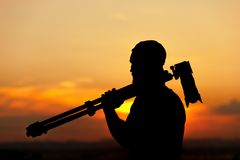 Male photographer holding camera and tripod. Silhouette of professional male photographer holding camera and tripod, looking into the distance at sunset time Stock Photography