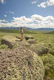 Male photographer by large rocks and mountains in Centennial Valley near Lakeview, MT Royalty Free Stock Images