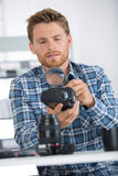 Male photographer repairing dslr at workplace Royalty Free Stock Image