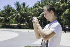 Male photographer, side view of a man holding camera in his hands Royalty Free Stock Photo
