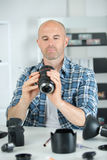 Male photographer soldering lens at workplace. Male photographer soldering lens at his workplace Royalty Free Stock Photos