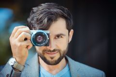 Male photographer taking picture. Portrait of handsome man with camera outdoors Royalty Free Stock Photography