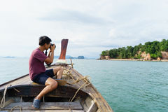 Male photographer taking a shot of island. Male photographer taking pictures of the beautiful beach island from the fishing boat Royalty Free Stock Images