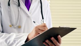 Male physician doctor writing rx prescription on clipboard for his patients stock footage