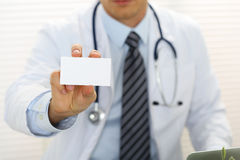 Male physician hand holding and giving white blank calling card Royalty Free Stock Photography