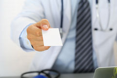 Male physician hand holding and giving white blank calling card Stock Image