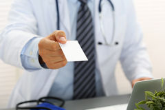 Male physician hand holding and giving white blank calling card Stock Photography