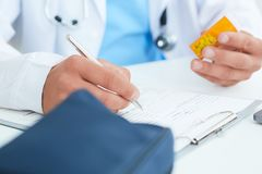 Male physician medicine doctor or pharmacist sitting at worktable, holding jar or bottle of pills in hand and writing. Prescription on special form. Just hand Stock Photography