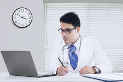 Male physician with notebook in office Royalty Free Stock Photo