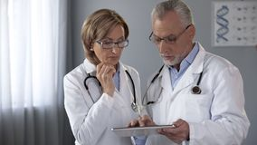 Male physician showing analysis results on tablet to his female colleague. Stock photo royalty free stock photos