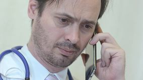 Male physician talking on the phone in the office. stock video footage