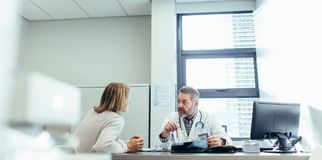 Doctor explaining diagnosis to female patient royalty free stock images