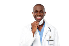 Male physician wearing surgical mask. African male doctor removing his surgical mask Stock Photos