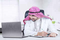 Male physician works with laptop in clinic. Picture of middle eastern physician works with laptop computer on the table in the clinic Royalty Free Stock Image