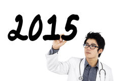 Male physician writes number 2015 on whiteboard Stock Images