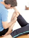 Male physio göra en massage arkivbild