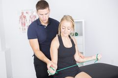 Male physio therapist and woman helping patient. A male physio therapist and women helping patient Royalty Free Stock Image