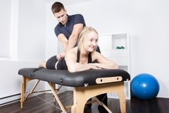 Male physio therapist and woman helping patient. A male physio therapist and women helping patient Stock Images