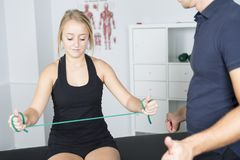 Male physio therapist and woman helping patient Stock Photos