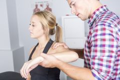 Male physio therapist and woman helping patient. A male physio therapist and women helping patient Stock Image