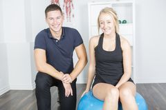 Male physio therapist and woman helping patient Stock Image