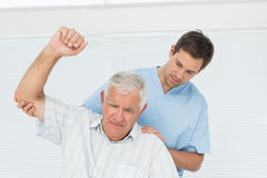 Male physiotherapist assisting senior man to raise hand Royalty Free Stock Photo