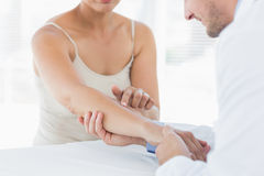 Male physiotherapist examining hand of woman Stock Image