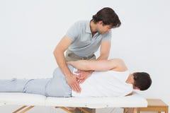 Male physiotherapist examining mans back Stock Image