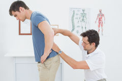 Male physiotherapist examining mans back in office. Side view of a male physiotherapist examining mans back in the medical office Royalty Free Stock Photo
