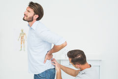 Male physiotherapist examining mans back. Side view of a male physiotherapist examining mans back in the medical office Royalty Free Stock Image