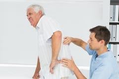 Male physiotherapist examining senior mans back Stock Photography