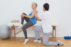 Male physiotherapist examining senior womans back Royalty Free Stock Images