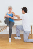 Male physiotherapist examining senior womans back Stock Images