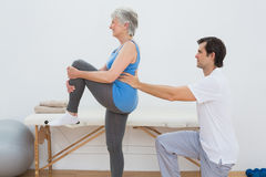 Male physiotherapist examining senior womans back. In the medical office Royalty Free Stock Photo