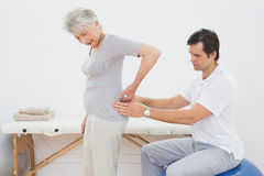 Male physiotherapist examining senior womans back Stock Image