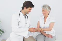 Male physiotherapist examining a senior womans wrist Stock Image