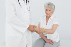 Male physiotherapist examining a senior womans wrist Stock Photos