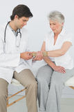 Male physiotherapist examining a senior womans wrist Royalty Free Stock Photos