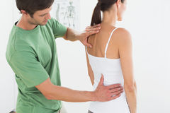 Male physiotherapist examining womans back Royalty Free Stock Image