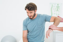Male physiotherapist examining a young mans arm Stock Image
