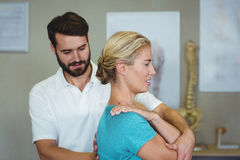 Male physiotherapist giving arm massage to female patient. In clinic Royalty Free Stock Images