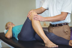 Male physiotherapist giving knee massage to female patient Royalty Free Stock Photo