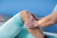 Male physiotherapist giving knee massage to female patient. In clinic Royalty Free Stock Photo