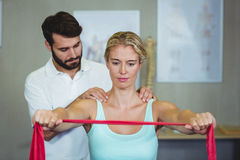 Male physiotherapist giving shoulder massage to female patient. In clinic Royalty Free Stock Photography
