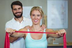 Male physiotherapist giving shoulder massage to female patient. In clinic Royalty Free Stock Photos