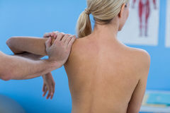 Male physiotherapist giving shoulder massage to female patient. In clinic Stock Images