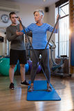 Male physiotherapist helping patient in performing exercise with resistance band. In clinic Stock Photos