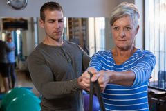 Male physiotherapist helping patient in performing exercise with resistance band Royalty Free Stock Image