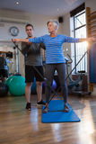 Male physiotherapist helping patient in performing exercise with resistance band Stock Photo